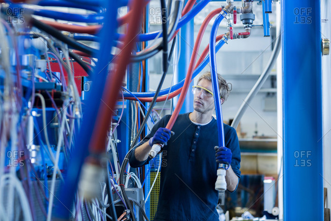 Factory technician inspecting network cables