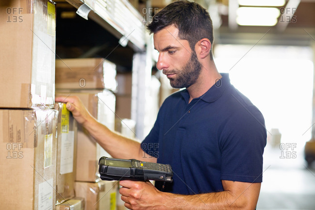 Warehouse worker using barcode scanner in distribution warehouse