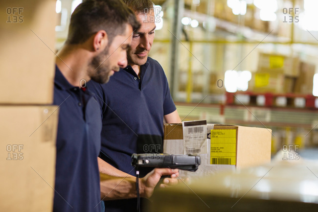 Male warehouse workers using barcode scanner in distribution warehouse