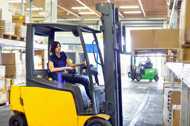 Female forklift truck driver working in distribution warehouse