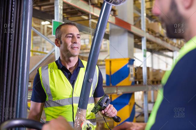 Supervisor instructing male forklift truck driver in distribution warehouse