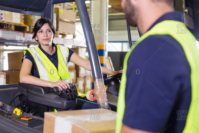Supervisor instructing female forklift truck driver in distribution warehouse