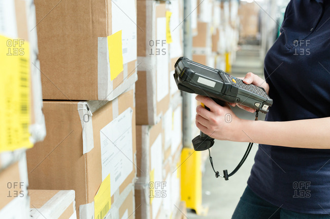 Warehouse worker using barcode scanner on box in distribution warehouse