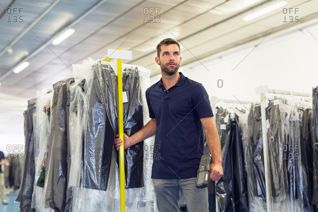 Warehouse worker pulling garment clothes rail in distribution warehouse
