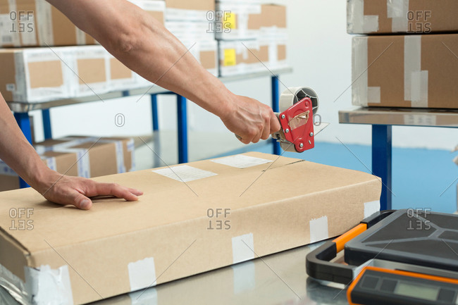 Hands of warehouse worker taping parcel in distribution warehouse