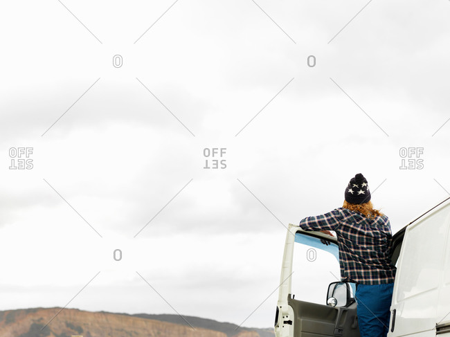 Rear view of young woman looking out from camper van, Point Addis, Anglesea, Victoria, Australia