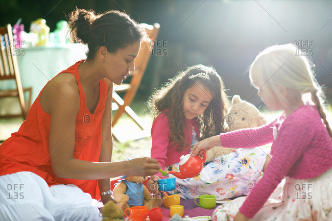 Mother and two girls playing picnics at garden birthday party