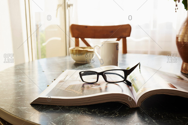 Open book on table with spectacles