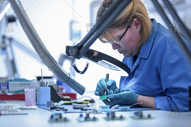 Female worker assembling electronics in electronics factory