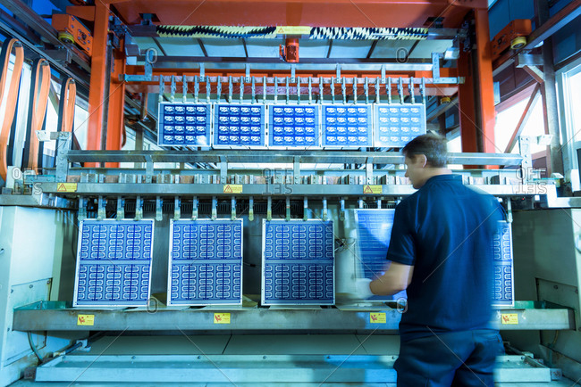 Worker loading circuit boards into processing machine