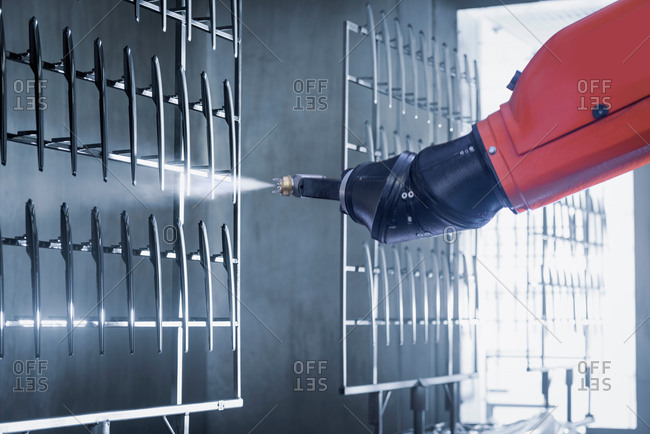 Robot spray painting automotive parts in spray paint factory, close up