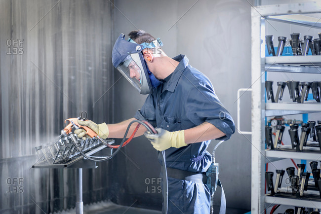 Worker paint spraying automotive parts in spray paint factory