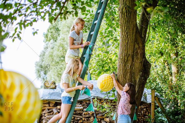 Girls decorating  tree in garden for summer party