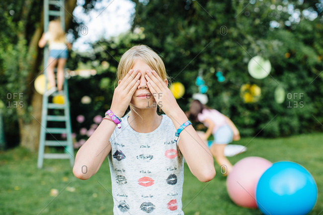 Girl covering eyes at summer party