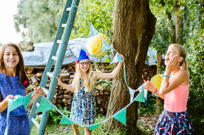 Girls string up bunting for summer party
