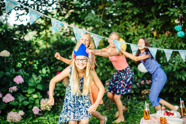 Girls dancing under bunting at summer garden party