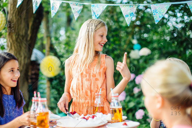Girl with a icing on her finger at a summer garden party