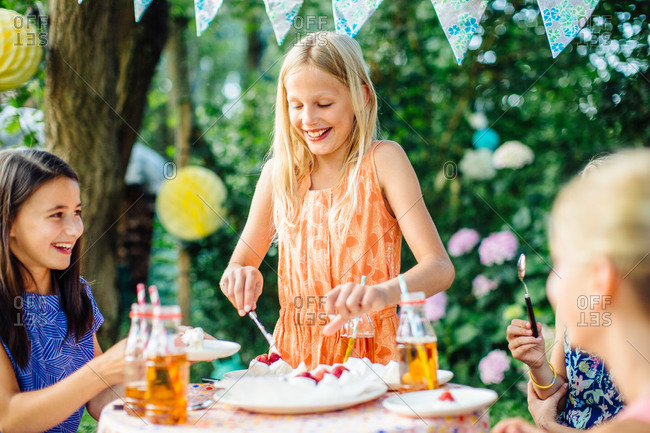 Girl serving cake at a summer garden party