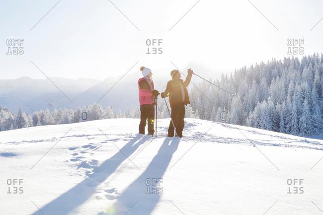 Senior couple on snow covered landscape holding walking poles looking away, Sattelbergalm, Tyrol, Austria
