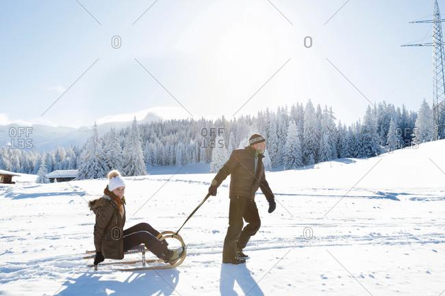 Side view of senior man pulled senior woman on sledge, Sattelbergalm, Tyrol, Austria