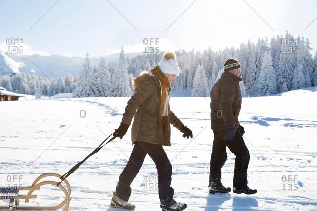 Side view of senior couple on snowy landscape pulling sledge, Sattelbergalm, Tyrol, Austria