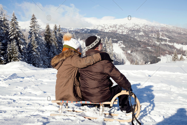 Snow capped mountains and rear view of senior couple sitting on sledge looking away, Sattelbergalm, Tyrol, Austria