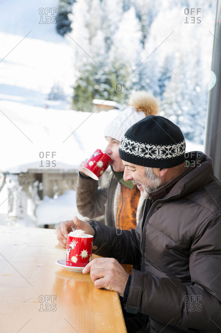 Side view of senior couple sitting at table drinking hot chocolate, Sattelbergalm, Tyrol, Austria
