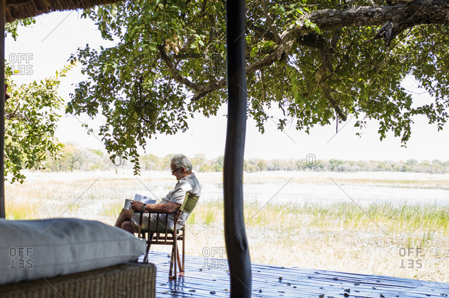 Senior man relaxing at safari lodge, Kafue National Park, Zambia