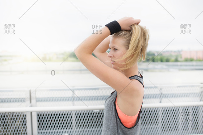 Young woman tying hair, preparing for workout, outdoors