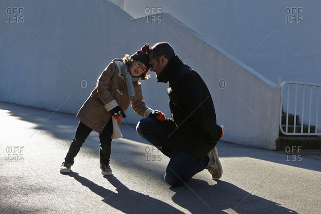 Father and daughter wearing duffle coat head to head in street