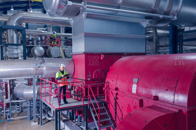 Engineer on access platform using digital tablet at geothermal power station