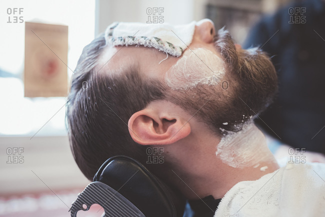 Male clients face with shaving cream and eyes covered in barber shop