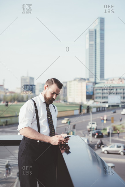 Businessman reading smartphone text update on office balcony