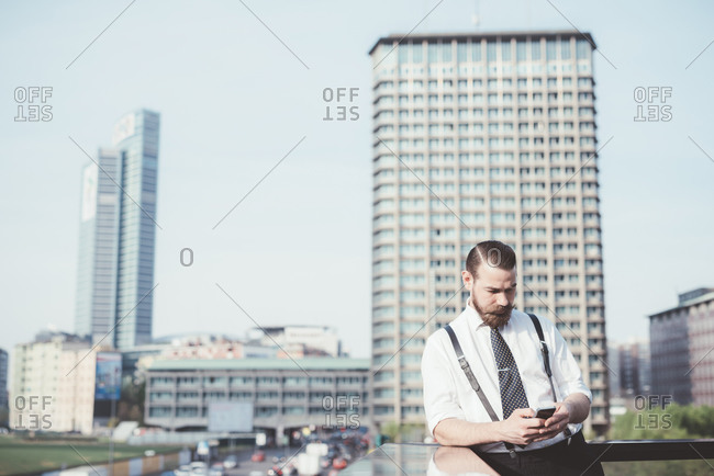 Stylish businessman reading smartphone text update on office balcony