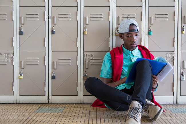 Student leaning against lockers, reading textbook