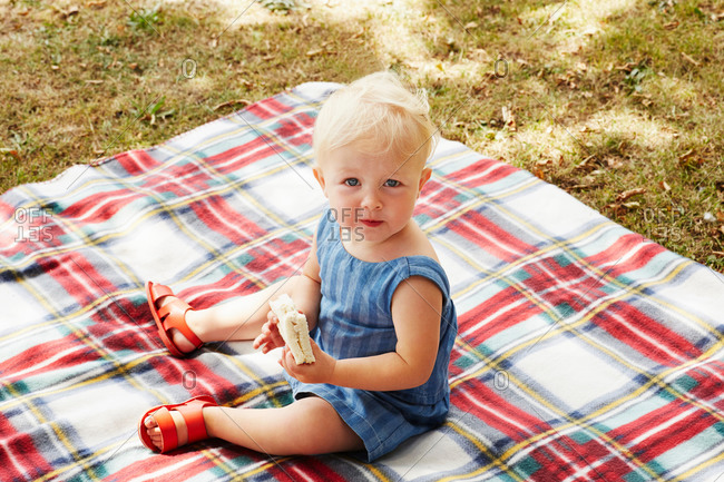 High angle view of baby girl sitting on picnic blanket looking ahead