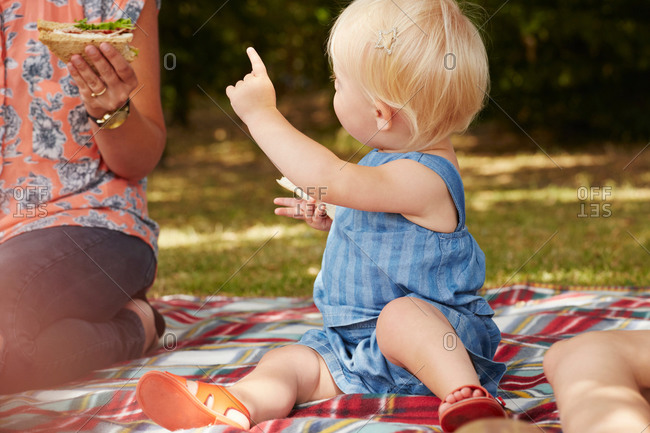 Woman and baby girl sitting on picnic blanket having picnic