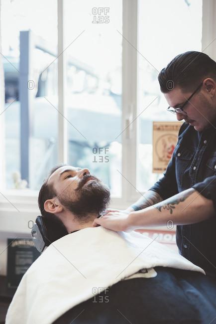 Barber preparing client towel for shaving in barber shop