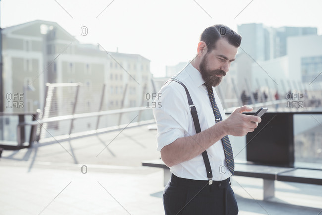 Businessman reading smartphone update on footbridge