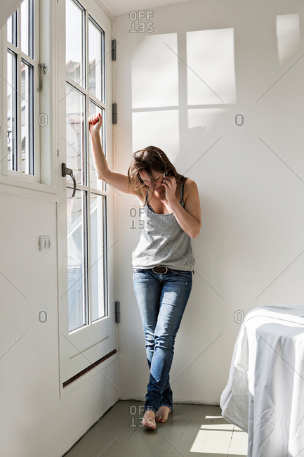 Mature woman standing in part furnished home, talking on mobile phone