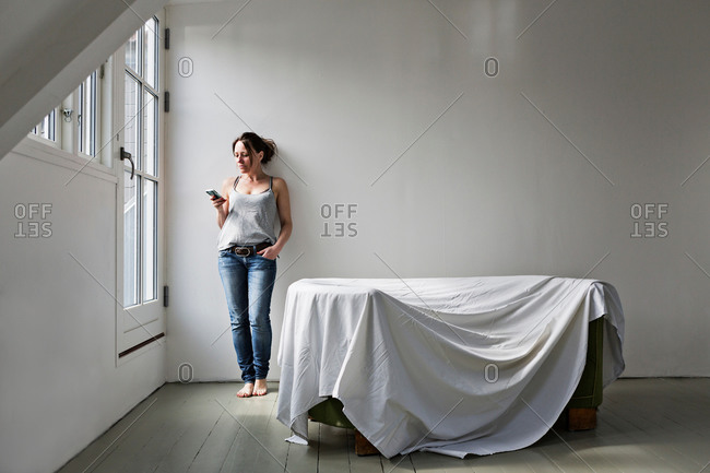 Mature woman standing in part furnished home, using mobile phone