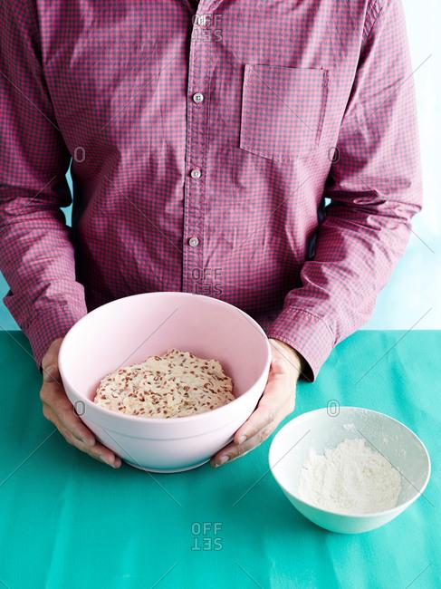 Man preparing no knead bread recipe step 1, bread dough