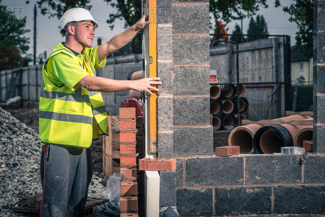Young man working on wall on construction site