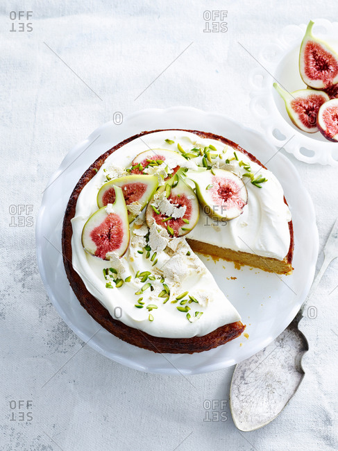 Overhead view of orange and almond cake with yoghurt cream, pistachios, figs and cake server