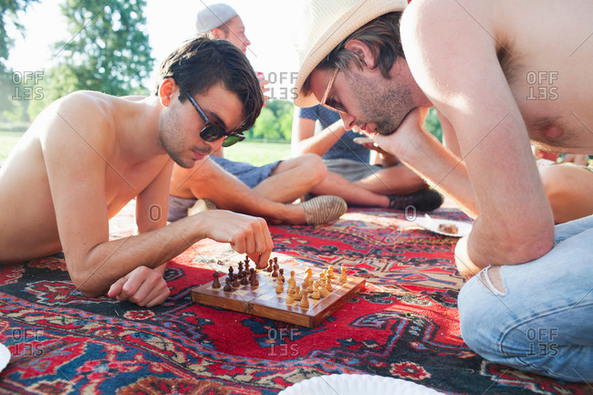 Two young men playing board game at sunset park party