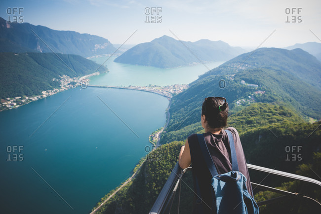 Mid adult woman on balcony looking out at Lake Lugano, Switzerland