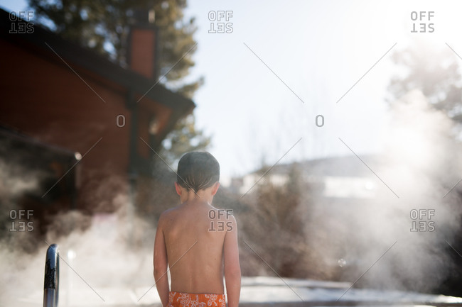Little boy getting into a hot tub outdoors in the winter