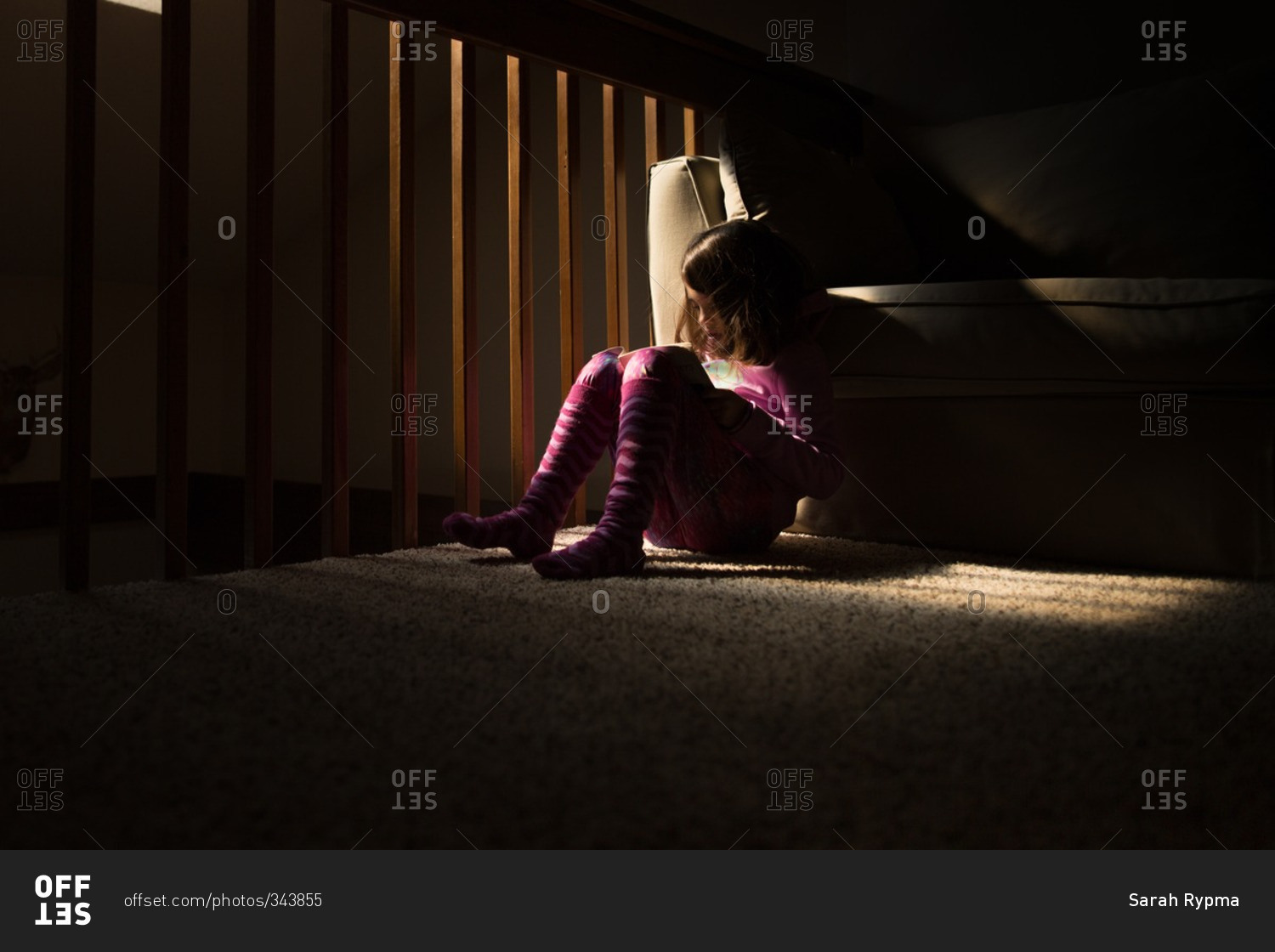 Little girl sitting in a dark room reading a book stock photo - OFFSET