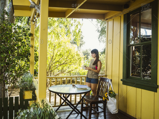 Young woman standing on porch with mug and phone