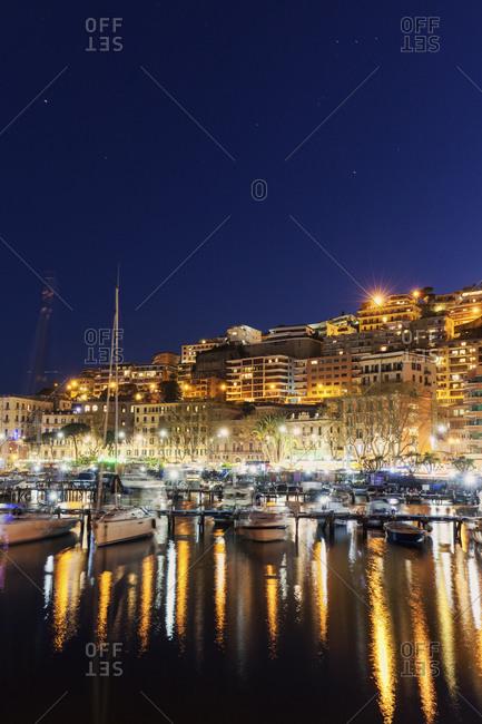 Boats in city marina at night